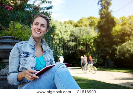 Smiling gorgeous female is enjoying free time and rest during her long awaited sparing weekend happy cheerful hipster girl with good mood is sitting with notepad in beautiful park during leisure