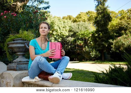 Thoughtful female ponders about book which she is reading during her free time in spring vacation gorgeous female is dreaming about something good while is sitting with notepad in park in summer