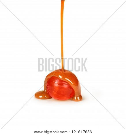 caramel candies and caramel sauce pouring isolated on a white background
