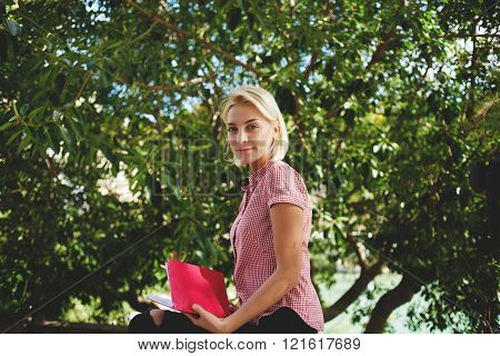 Attractive woman is posing while is sitting with book in park against green leaves during summer weekend gorgeous female look at the camera while she is relaxing in the fresh air during free time