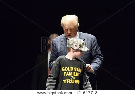 Saint Louis, MO, USA - March 11, 2016: Donald Trump signs shirt of boy at the Peabody Opera House in Downtown Saint Louis.
