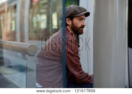 Hipster man dressed in a brown leather jacket and stylish hat is sitting on a bench outdoors in spring day bearded adult male is thinking about something while waiting for a someone in the fresh air