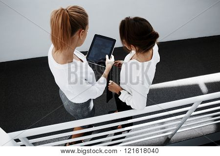 Top view of woman financier is holding touch pad with mock up copy space screen for your advertising text message. Two female entrepreneurs are reading financial news in internet via digital tablet