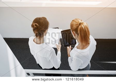 Top view of a two female successful economists are holding paper documents and digital tablet with copy space for advertising text message while are standing in office interior during break at job