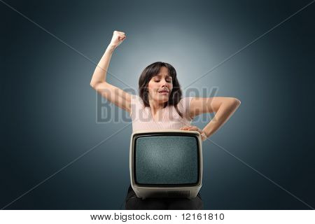 Angry woman punching an old television