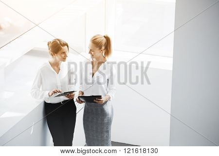 Smiling businesswoman is holding folder with important documents and contracts while her secretary is searching on digital tablet needed information for future meetings with international partners