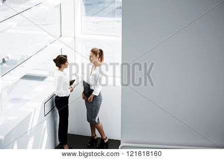 Two female having pleasant conversation while they are standing in hallway interior near window. Businesswoman satisfied positive feedback from customers which she is reading secretary from touch pad