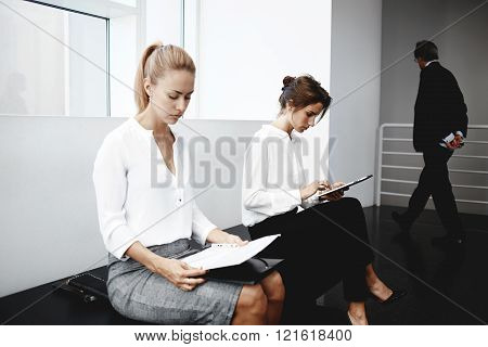 Young woman is reading paper documents while female near is searching information in network via digital tablet. Women are preparing for interview while they are sitting in corridor of big company