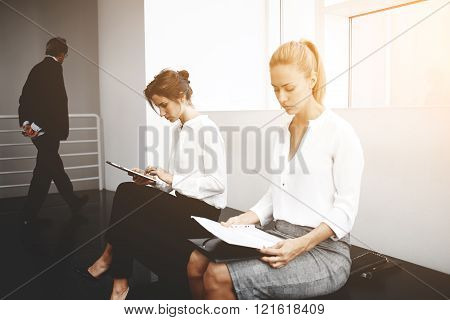Young female is using portable digital tablet while woman near is reading paper documents before interview with employer. Serious women are preparing to important negotiations with foreign investors
