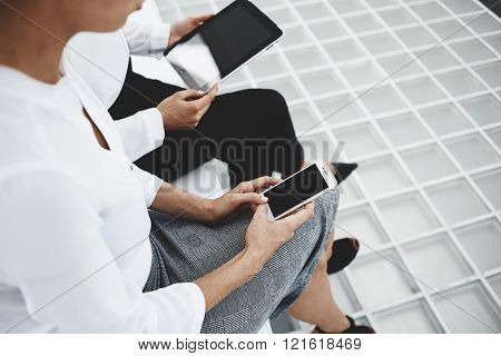 Closely of women are working on smart phone and digital tablet with copy space on the screens. Two female managers are browsing information on web via cell telephone and touch pad before conference