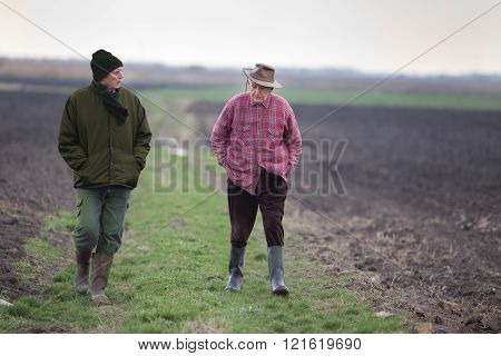 Two senior peasants walking on the field in winter time