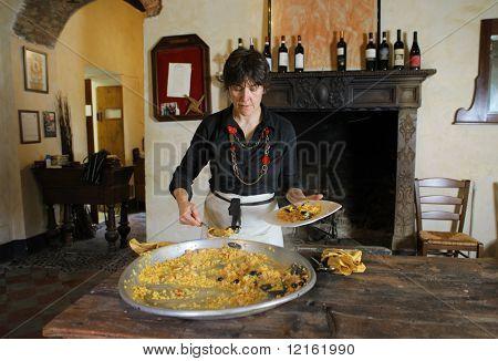 smiling woman preparing a paella valenciana