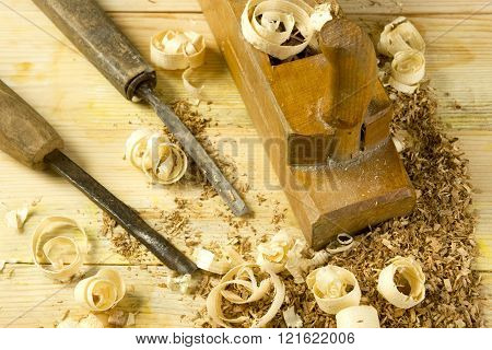 Carpenter tools on wooden table with sawdust. Craftperson workplace top view