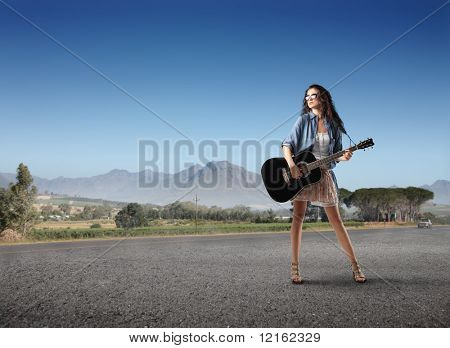 Woman holding a guitar on a countryside road