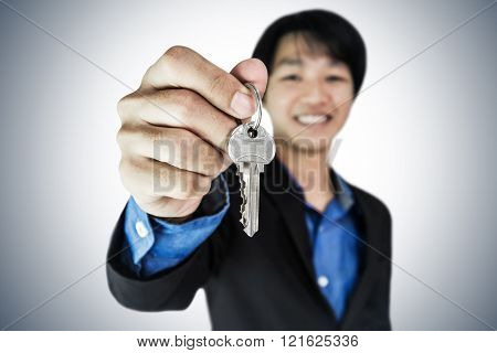 Businessman holding keys with smiling face, selective focus