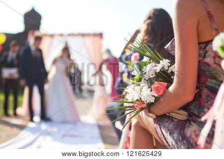 Wedding ceremony outdoors, focus on flowers bouquet
