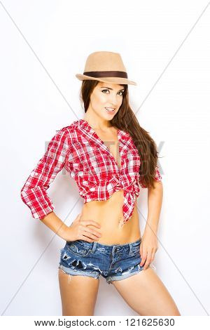 woman in tied shirt shorts and hat
