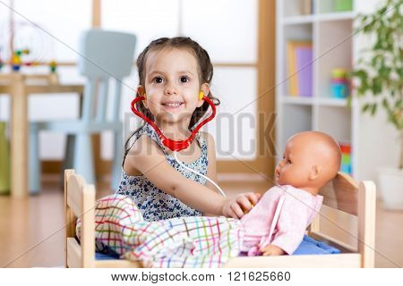 child girl playing doctor role game examining her doll using stethoscope sitting in playroom at home