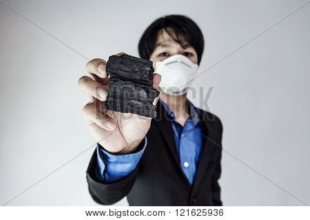 Young business Asian guy wearing protect air mask, showing coal, selective focus on coal