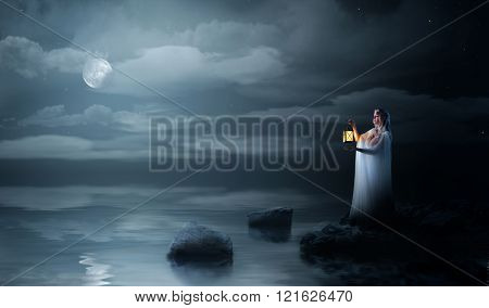 Young elven girl with lantern at night sea shore