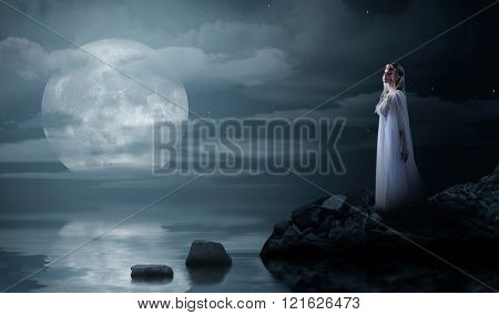 Young elven girl at night sea shore