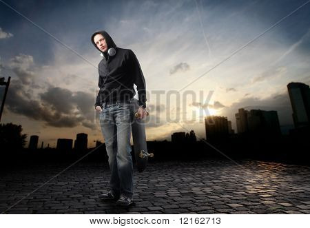 Young man in street-wear standing on a city street