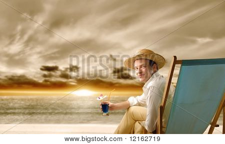 Young man sitting on a deckchair in front of the sea and holding a glass of cocktail