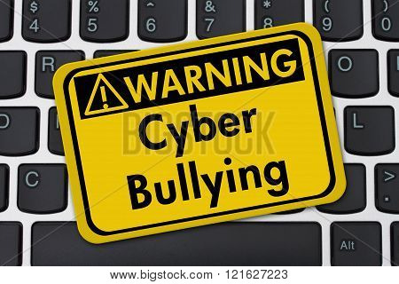 Cyber Bullying Warning Sign A yellow warning sign with text Cyber Bullying on a keyboard