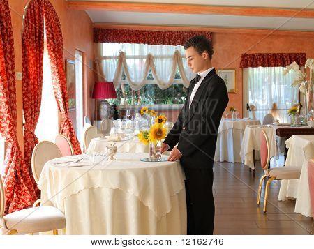 Waiter preparing tables in a restaurant