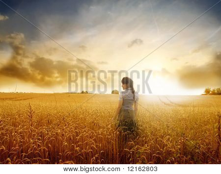 Young woman standing on a wheat field with sunrise on the background