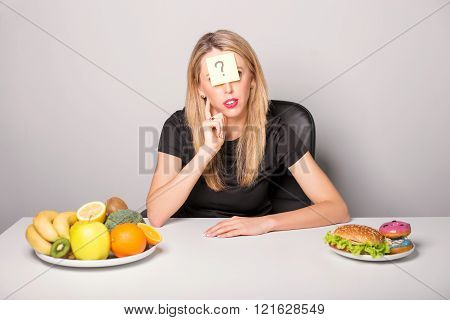 Woman with sticky note and question mark on her forehead choosing between healthy and unhealthy food