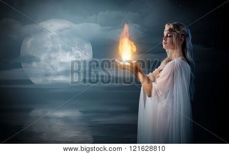 Young elven girl holding fire in palms at sea shore