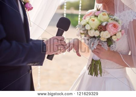 The groom wears a wedding ring on the finger of the bride