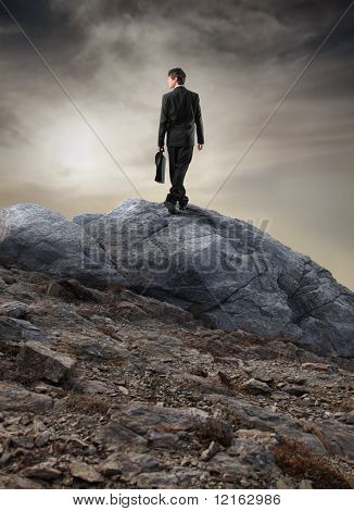 Businessman walking on a rock in the mountains
