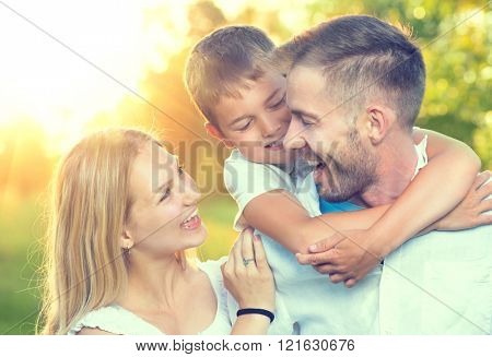 Happy young family having fun outdoors. Joyful young family father, mother and little son playing together in spring park. Mom, Dad and kid laughing and hugging, enjoying nature outside. Piggyback