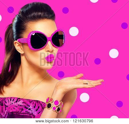 Beauty surprised fashion model girl wearing purple sunglasses, with bright makeup showing empty copy space on open hand palm for text over pink background. Emotions. Beautiful woman, summer fashion