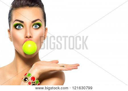 Beauty surprised fashion funny model girl with green bubble of chewing gum and bright makeup showing empty copy space on the open hand palm for text over white background. Emotions. Beautiful woman