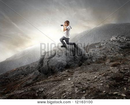 Criança usando uma câmera em uma rocha nas montanhas