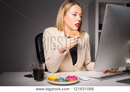 Woman in office eating junk food