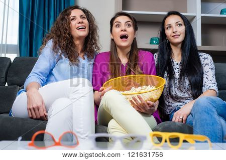 Three smiling girlfriends watching a movie