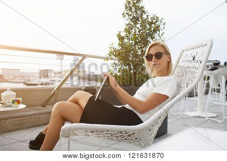 Fashionable woman is relaxing with touch pad in comfortable coffee shop outdoors.