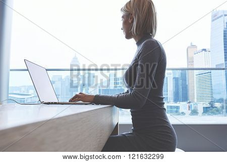 Young businesswoman is thinking about something during work on net-book