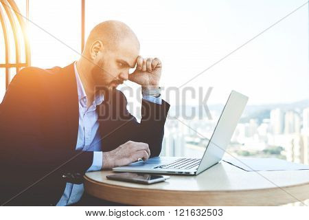 Young man professional in the economic field is searching needed information on laptop computer