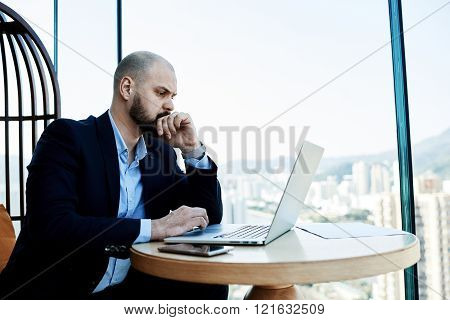 Young male economist reading financial news on net-book about falling shares on exchange