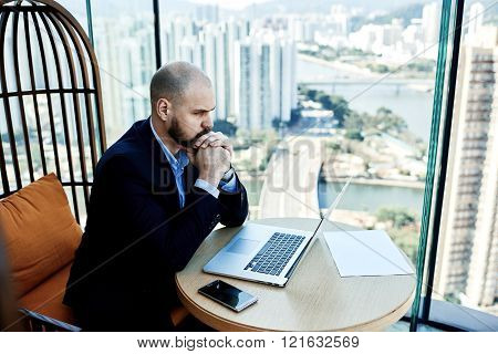 Man investor reading negative news on net-book about falling shares on stock exchanges.