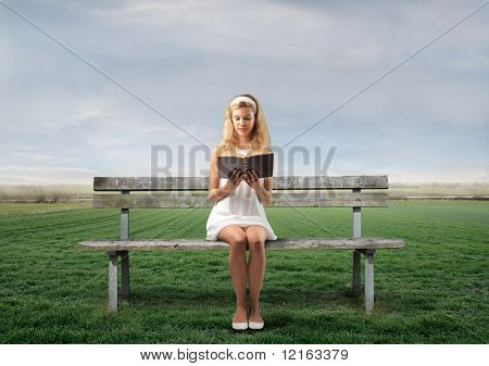 Young woman sitting on a park bench and reading a book