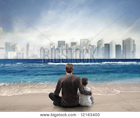 Father and son sitting on a beach looking over a city