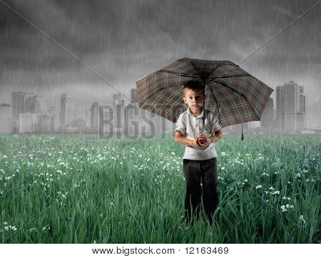 Child standing under an umbrella on a green meadow with stormy sky on the background