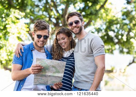 Hip friends checking map outdoors and smiling