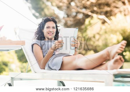 Portrait of young woman reading magazine and relaxing on a sun lounger near poolside